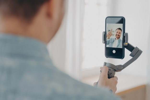 Vue arrière du beau jeune homme brunete souriant avec chaume faisant selfie sur smartphone avec stabilisateur de cardan à la maison et gesticulant signe ok, porte des vêtements décontractés. notion de blog