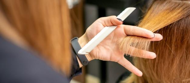 Vue arrière du coiffeur coupe les cheveux rouges ou bruns à la jeune femme dans un salon de beauté. coupe de cheveux dans un salon de coiffure