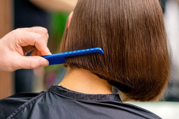 Vue arrière du coiffeur masculin peignant les cheveux courts de femme dans le salon
