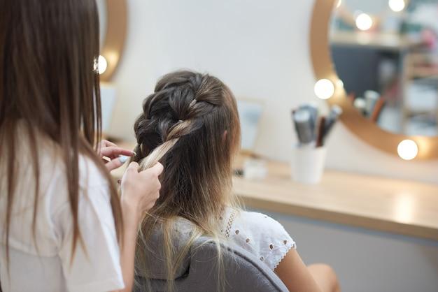 Vue de l'arrière du coiffeur tressant deux épillets au client dans un salon de beauté