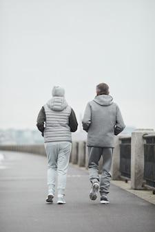 Vue arrière du couple d'âge mûr actif en vêtements de sport gris jogging le long de la rivière dans un matin sombre