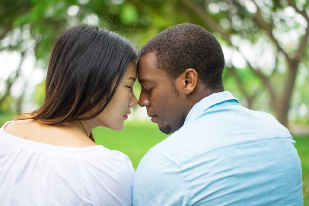 Vue arrière du couple d'amoureux paisible touchant les fronts et profiter du temps ensemble