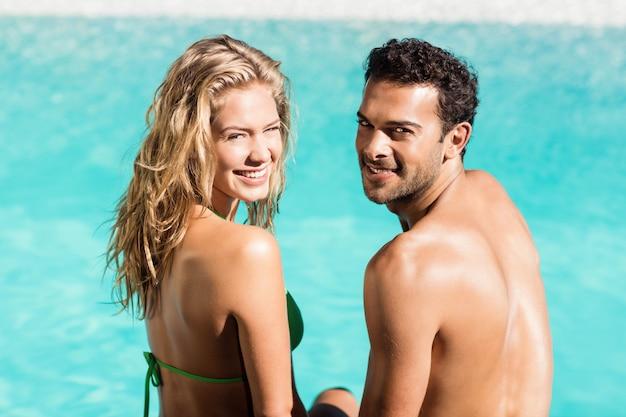Vue arrière du couple assis au bord de la piscine et regardant la caméra