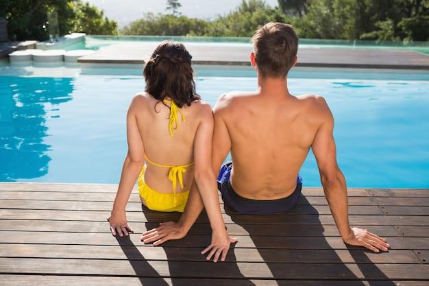 Vue arrière du couple assis au bord de la piscine