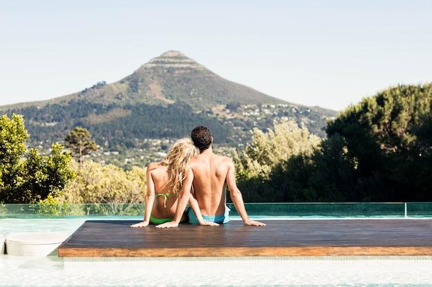 Vue arrière du couple assis devant la piscine en regardant le paysage