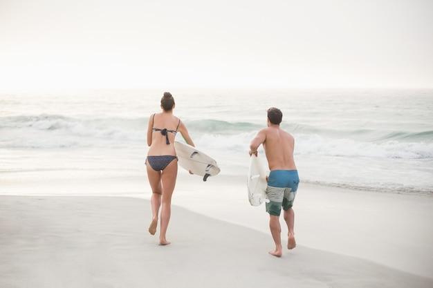 Vue arrière du couple en cours d'exécution avec une planche de surf sur la plage