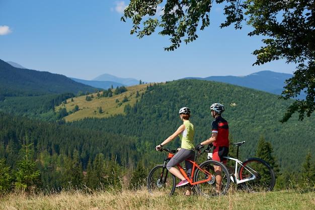 Vue arrière du couple de jeunes motards, homme et femme debout avec des vélos sur une colline herbeuse bénéficiant d'une vue fantastique sur la magnifique chaîne de montagnes mode de vie actif, tourisme et concept de relations familiales heureuses.