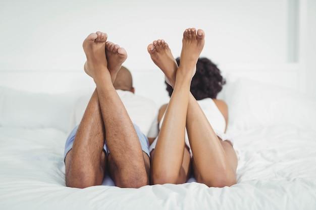 Vue arrière du couple sur le lit avec les jambes surélevées à la maison