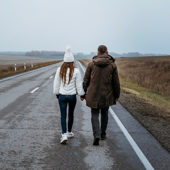 Vue arrière du couple main dans la main sur la route