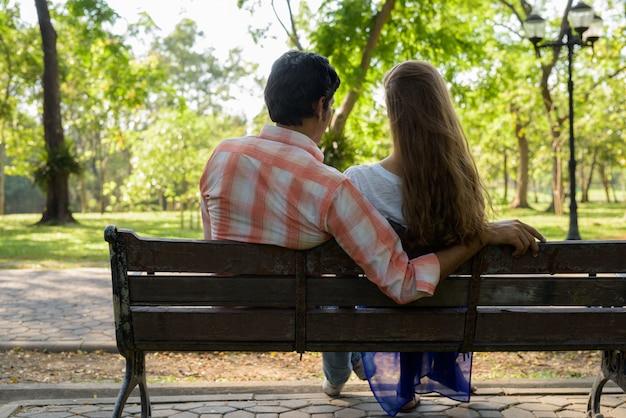 Vue arrière du couple multiethnique assis sur un banc en bois