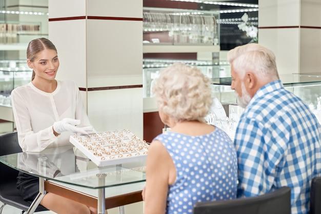 Vue arrière du couple de personnes âgées choisissant des anneaux de mariage