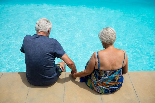 Vue arrière du couple de personnes âgées se détendre au bord de la piscine