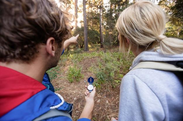 Vue arrière du couple de randonnée tenant une boussole et pointant vers l'avant