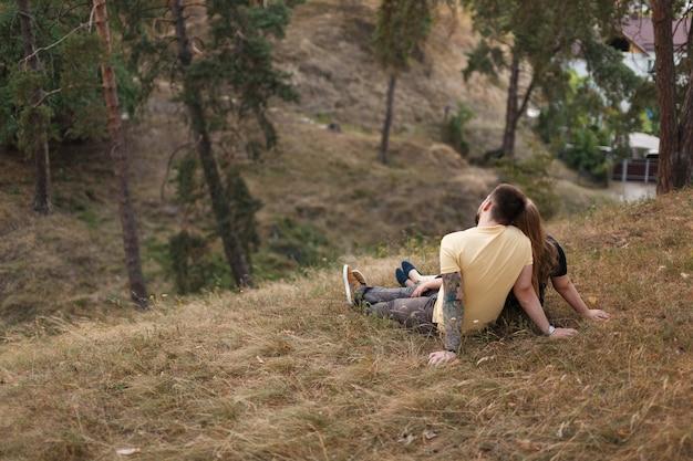 Vue arrière du couple romantique amoureux assis sur la colline en été