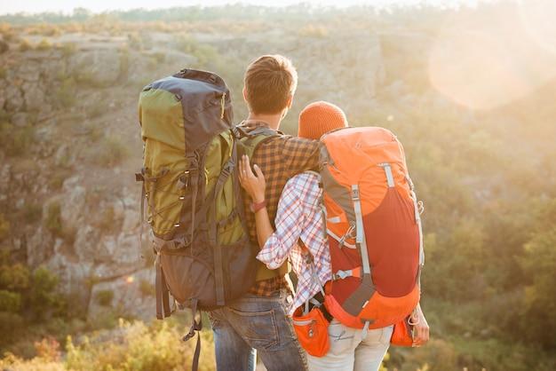 Vue arrière du couple avec des sacs à dos dans les montagnes