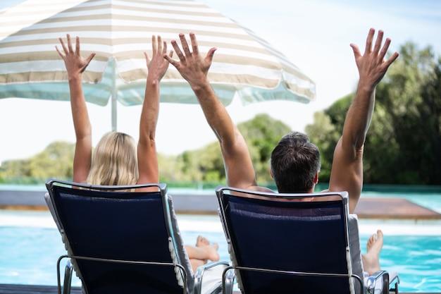 Vue arrière du couple se détendre sur une chaise longue avec la main levée