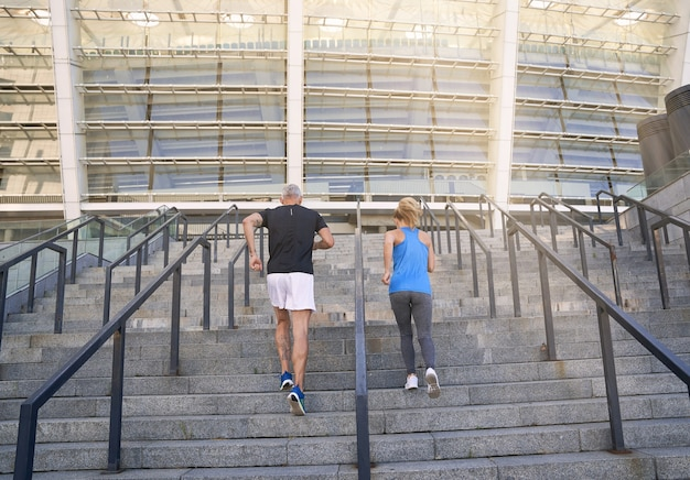 Vue arrière du couple sportif en jogging sportswear tout en s'entraînant ensemble à l'extérieur de la ville