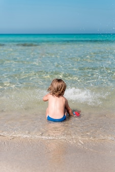 Vue arrière du gamin assis sur le rivage