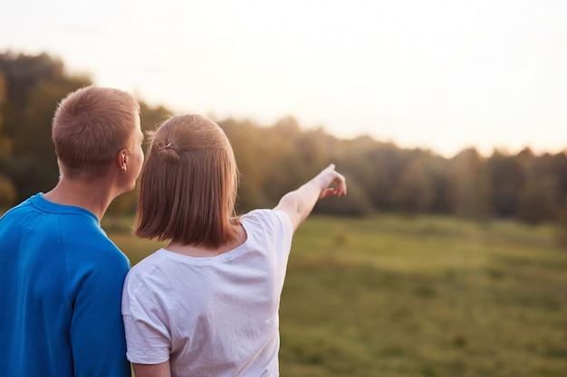 Vue arrière du gars affectueux et sa petite amie se tiennent étroitement l'un à l'autre