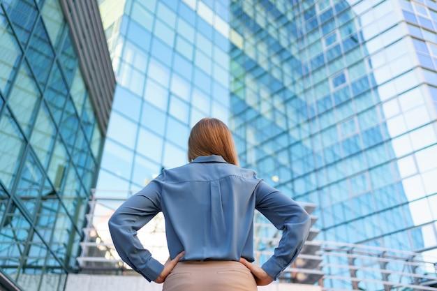 Vue arrière du gestionnaire prospère regardant le bâtiment des affaires de la ville moderne.