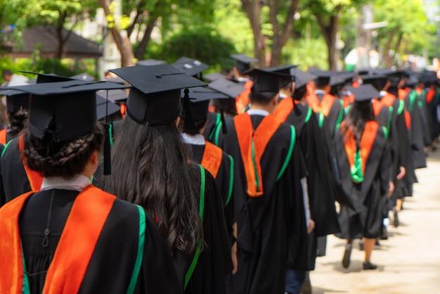 Vue arrière du groupe de diplômés universitaires en robes noires s'aligne pour le diplôme lors de la cérémonie de remise des diplômes universitaires. félicitation de l'éducation concept, étudiant, réussi à étudier.