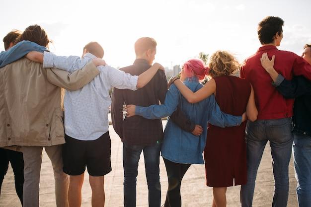 Vue arrière du groupe de jeunes diversifiés. armez-vous. soutien de l'unité. amitié ensemble