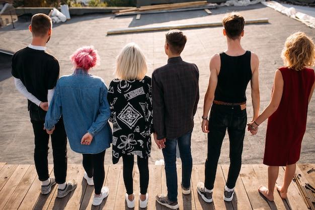 Vue arrière du groupe de jeunes diversifiés. l'unité soutient le concept d'unité d'amitié de confiance