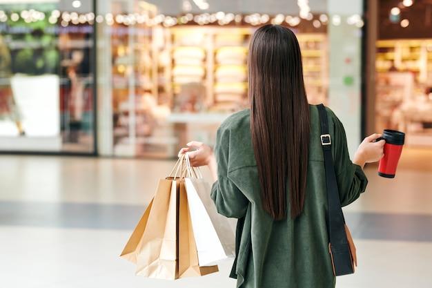 Vue arrière du jeune acheteur contemporain avec des cheveux longs foncés transportant des sacs en papier et une tasse rouge avec boisson tout en se déplaçant le long du centre commercial