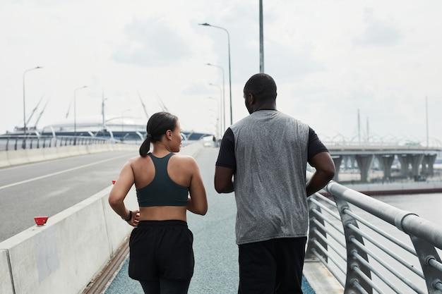 Vue arrière du jeune couple africain courant le matin à l'extérieur