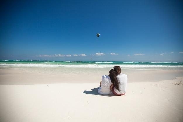Vue arrière du jeune couple assis sur une plage tropicale blanche
