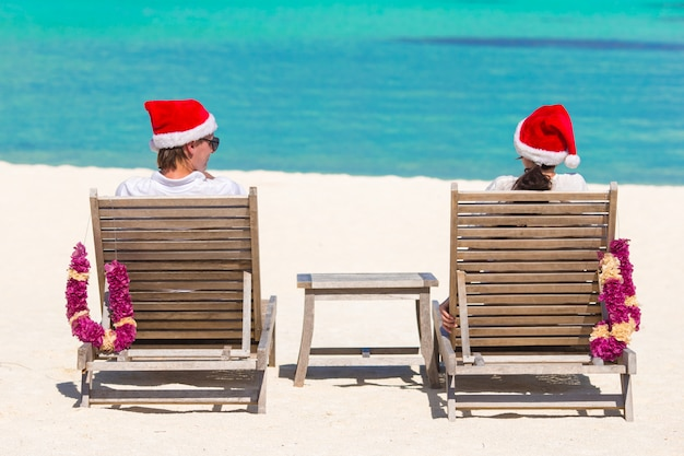 Vue arrière du jeune couple en chapeaux santa se détendre sur une plage tropicale pendant les vacances de noël