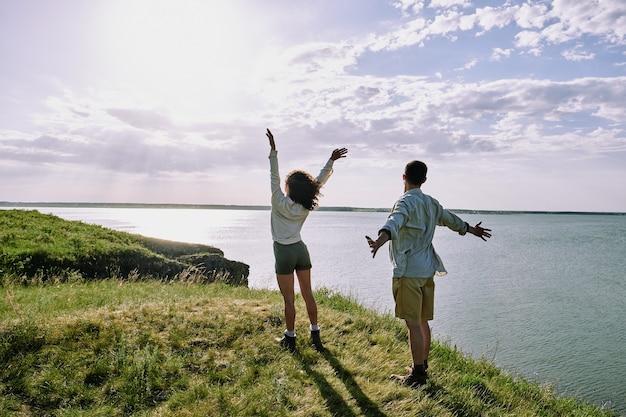 Vue arrière du jeune couple extatique en tenue décontractée debout sur l'herbe verte sur la rive et profiter d'un week-end ensoleillé en bord de mer