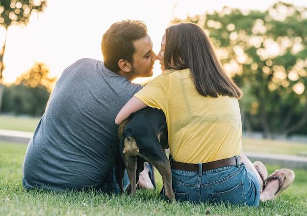 Vue arrière du jeune couple heureux s'embrassant avec leur chien dans le parc. jeune couple amoureux s'embrasser avec leur chien sur l'herbe.
