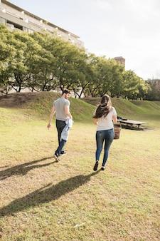 Vue arrière du jeune couple marchant dans le parc