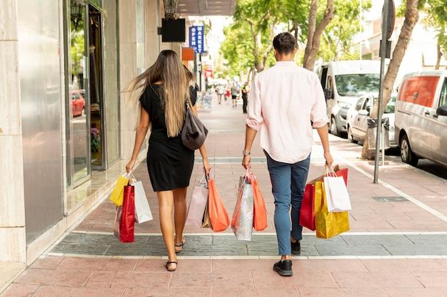 Vue arrière du jeune couple marchant dans la rue