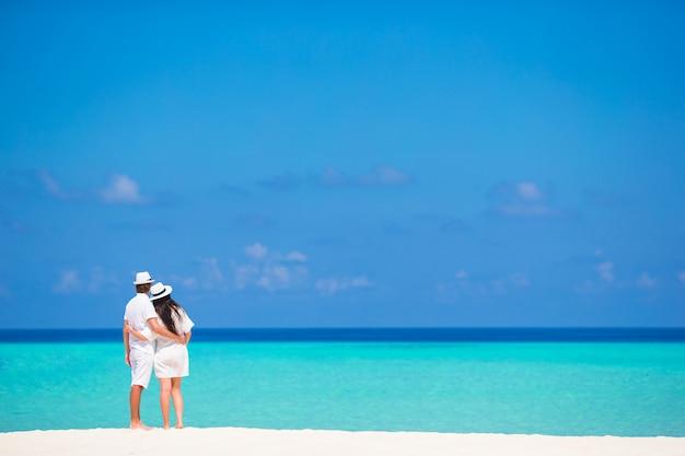 Vue arrière du jeune couple sur la plage blanche en vacances d'été