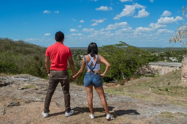 Vue arrière du jeune couple regardant l'horizon depuis les hauteurs de la colline