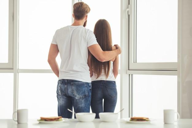 Vue arrière du jeune couple regardant par la fenêtre