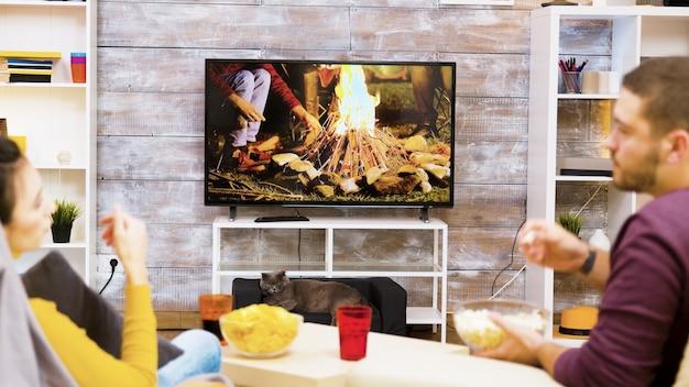Vue arrière du jeune couple se détendre sur une chaise en regardant la télévision tout en mangeant des chips et du pop-corn. chat devant la télé.