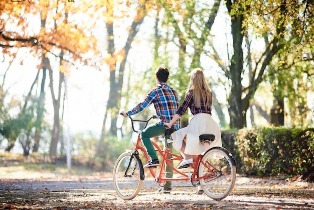 Vue arrière du jeune couple de touristes, homme et femme blonde vélo ensemble tandem double vélo rouge par parc ou forêt allée ensoleillée couverte de feuilles d'or à l'automne