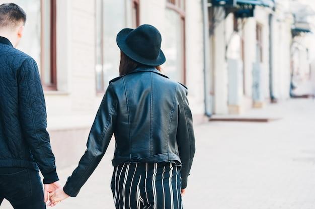 Vue arrière du jeune couple en vestes noires tenant la main fille au chapeau marchant le long de la rue