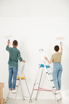 Vue arrière du jeune couple en vêtements décontractés debout sur escabeaux et mur de douleur avec rouleau à peinture tout en faisant l'intérieur de rêve dans un nouvel appartement