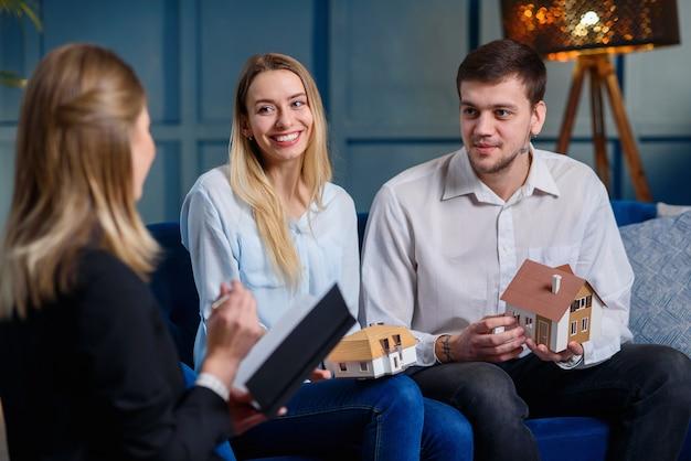 Vue arrière du jeune designer notant les souhaits d'un couple élégant handosme sur le futur design de la maison dans le cahier.