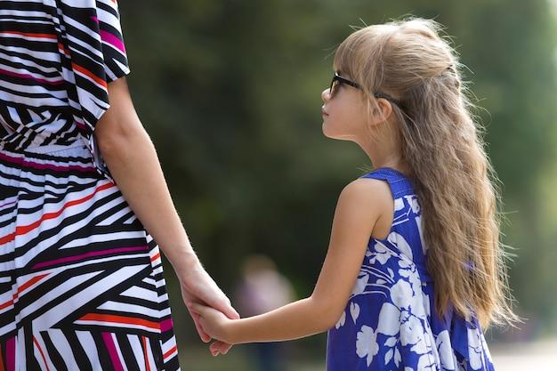 Vue arrière du jeune femme séduisante aux cheveux longs blonde et fille de petit enfant tenant les mains à l'extérieur.