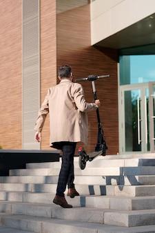 Vue arrière du jeune homme d'affaires élégant dans des vêtements décontractés intelligents transportant un scooter électrique tout en montant à l'étage pour entrer dans le centre de bureau
