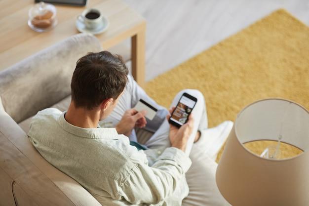Vue arrière du jeune homme assis sur un canapé avec téléphone portable et achats en ligne à l'aide de sa carte de crédit