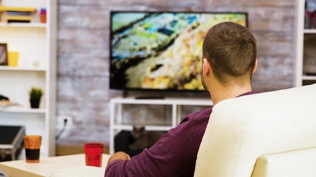Vue arrière du jeune homme assis sur une chaise en train de manger du pop-corn devant la télévision.
