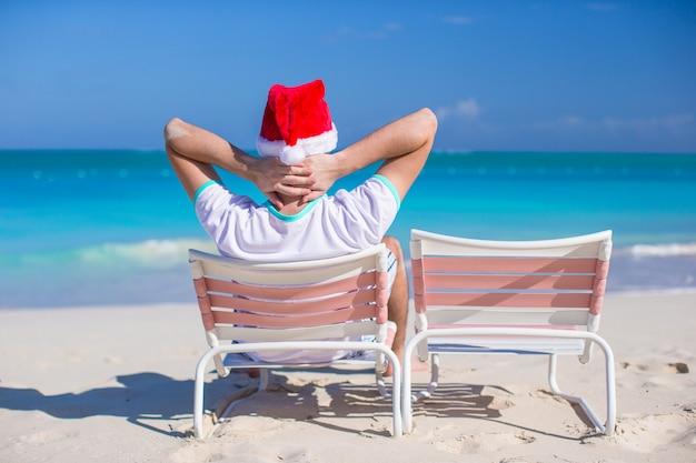 Vue arrière du jeune homme au chapeau de noël sur une chaise de plage