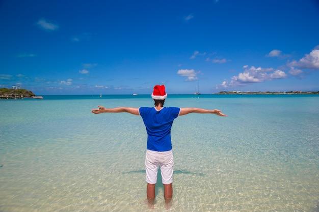 Vue arrière du jeune homme en bonnet de noel sur la plage tropicale