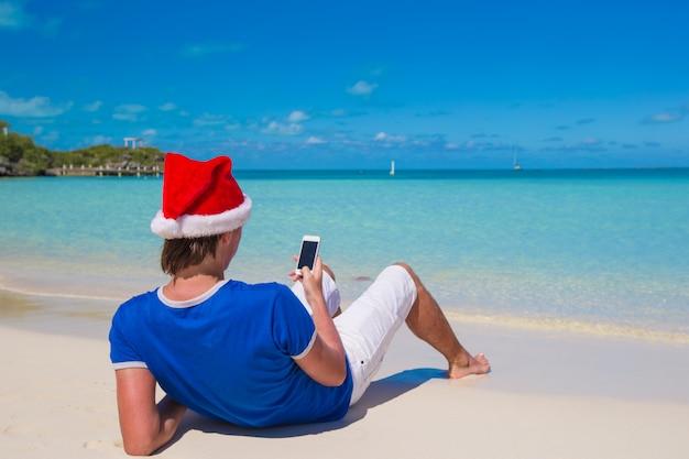 Vue arrière du jeune homme en bonnet de noel avec téléphone sur la plage des caraïbes tropicale